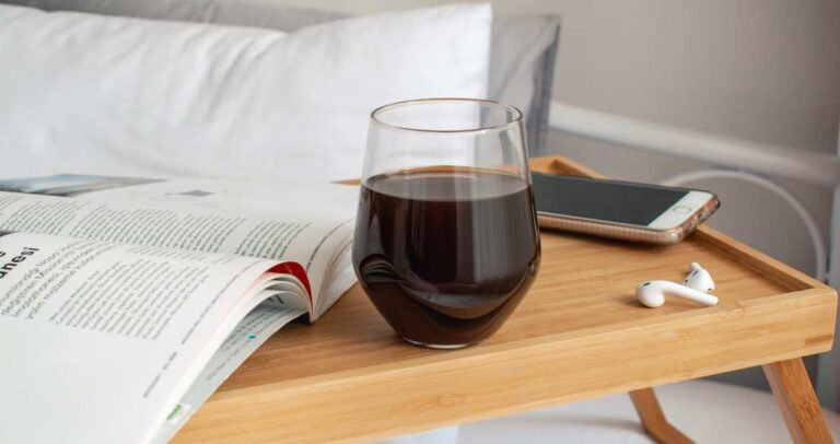 Wine in bedroom with airpods and magazine